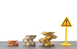 Pila della moneta ed etichetta di avvertimento rischiose su fondo bianco Immagini Stock