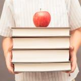 Pila della tenuta del bambino di libri spessi con la mela sulla cima Fotografia Stock