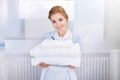 Pila della tenuta della domestica di asciugamani Immagini Stock Libere da Diritti
