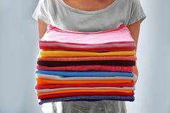 Pila della tenuta della donna di vestiti, Immagini Stock