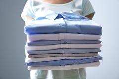 Pila della tenuta della donna di vestiti, Fotografie Stock Libere da Diritti