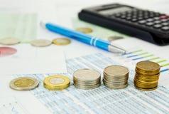 Pila delle monete e della penna sulla priorità bassa di affari Immagini Stock