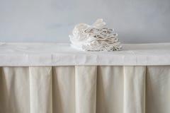 Pila di asciugamani del panno sulla tavola bianca nel ristorante Fotografia Stock