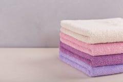Pila di asciugamani di bagno variopinti su fondo leggero Fotografie Stock
