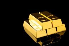 Pila di barre di oro brillanti su fondo nero fotografia stock libera da diritti