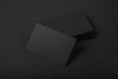 Pila di biglietti da visita neri in bianco sul fondo del tessuto Fotografia Stock