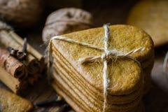 Pila di biscotti fatti domestici di Natale del pan di zenzero nello stile scandinavo legati con cordicella, bastoni di cannella,  Fotografia Stock