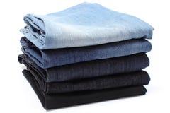 Pila di blue jeans su fondo bianco Fotografia Stock Libera da Diritti