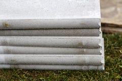 Pila di bordo concreto sull'erba Fotografia Stock Libera da Diritti