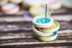 Pila di bottoni variopinti con l'ago di cucito Fotografia Stock Libera da Diritti