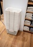 Pila di canestri bianchi sul pavimento di legno nel dettagliante dell'abbigliamento immagini stock libere da diritti