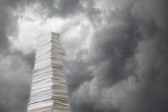 Pila di carta contro un cielo tempestoso Immagini Stock