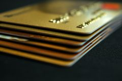 Pila di carte di credito dell'oro su fondo scuro, fine su spirito di vista fotografie stock libere da diritti