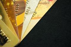 Pila di carte di credito dell'oro su fondo scuro, fine su spirito di vista Fotografie Stock
