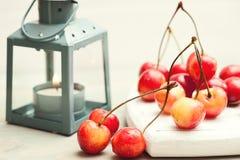 Pila di ciliege su fondo di legno bianco con la lanterna accesa Immagine Stock