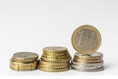 Pila di euro monete sui soldi bianchi dell'euro del fondo Immagine Stock Libera da Diritti