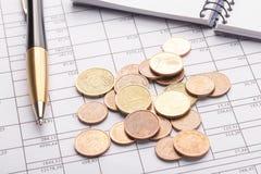Pila di euro euro monete sulla vecchia tavola di legno nera Penna, taccuino e documenti contabili con i numeri immagini stock