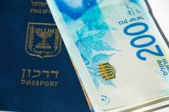 Pila di fatture di soldi israeliane dello shekel 200 e di passaporto israeliano Immagine Stock