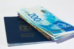 Pila di fatture di soldi israeliane dello shekel 200 e di passaporto israeliano Fotografie Stock Libere da Diritti