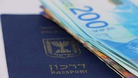Pila di fatture di soldi israeliane dello shekel 200 e passaporto israeliano - filtri la destra stock footage