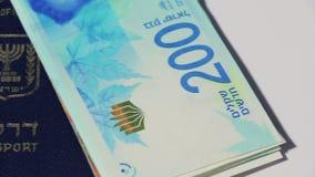 Pila di fatture di soldi israeliane dello shekel 200 e passaporto israeliano - filtri a sinistra archivi video