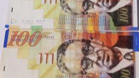 Pila di fatture di soldi israeliane 100 dello shekel - inclinazione giù archivi video