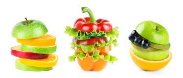Pila di fette miste di verdura e della frutta su bianco immagini stock libere da diritti