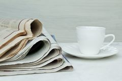 Pila di giornali con la tazza di caffè su fondo bianco fotografie stock