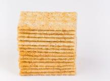 Pila di interi cracker organici freschi del grano su fondo bianco Fotografia Stock