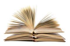 Pila di libri aperti su una priorità bassa bianca Immagine Stock