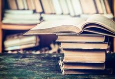 Pila di libri aperti sulla tavola invecchiata nella biblioteca Immagine Stock