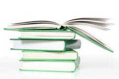 Pila di libri con il libro aperto Immagini Stock