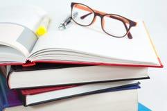 Pila di libri con il libro aperto ed i vetri Fotografia Stock