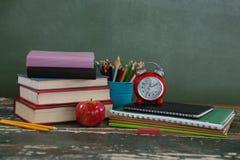 Pila di libri con il supporto della sveglia, della mela e della penna Fotografia Stock