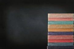 Pila di libri con la lavagna Immagine Stock