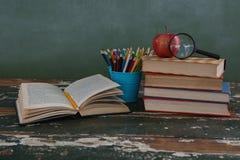 Pila di libri con la mela, la lente d'ingrandimento ed il supporto della penna Fotografia Stock