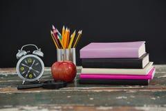 Pila di libri con la sveglia, la mela, la lente d'ingrandimento ed il supporto della penna Fotografie Stock Libere da Diritti