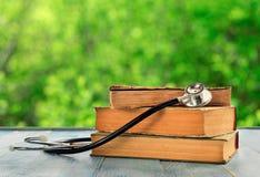 Pila di libri con lo stetoscopio sulla tavola di legno Fotografia Stock Libera da Diritti