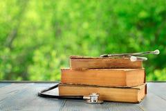 Pila di libri con lo stetoscopio sulla tavola di legno blu Immagine Stock Libera da Diritti
