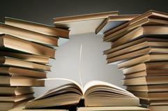 Pila di libri con uno aperto fra loro Fotografie Stock Libere da Diritti