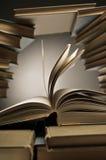 Pila di libri con uno aperto fra loro Immagini Stock Libere da Diritti