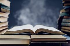 Pila di libri con uno aperto fra loro Fotografia Stock