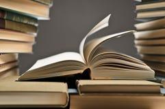Pila di libri con uno aperto fra loro Immagine Stock