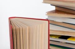 Pila di libri della libro con copertina rigida e di vecchio libro aperto sul fondo bianco della parete Ricerca di informazioni pe Immagini Stock Libere da Diritti