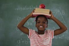 Pila di libri della tenuta della scolara con la mela sulla testa contro la lavagna Immagini Stock Libere da Diritti