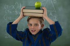 Pila di libri della tenuta dello scolaro con la mela contro la lavagna Immagine Stock Libera da Diritti