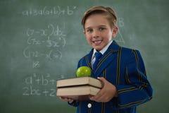 Pila di libri della tenuta dello scolaro con la mela contro la lavagna Fotografia Stock Libera da Diritti