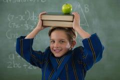 Pila di libri della tenuta dello scolaro con la mela sulla testa contro la lavagna Fotografia Stock