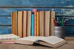 Pila di libri, di libro aperto e di supporto della penna Fotografia Stock