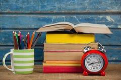 Pila di libri, di sveglia e di supporto della penna Fotografie Stock